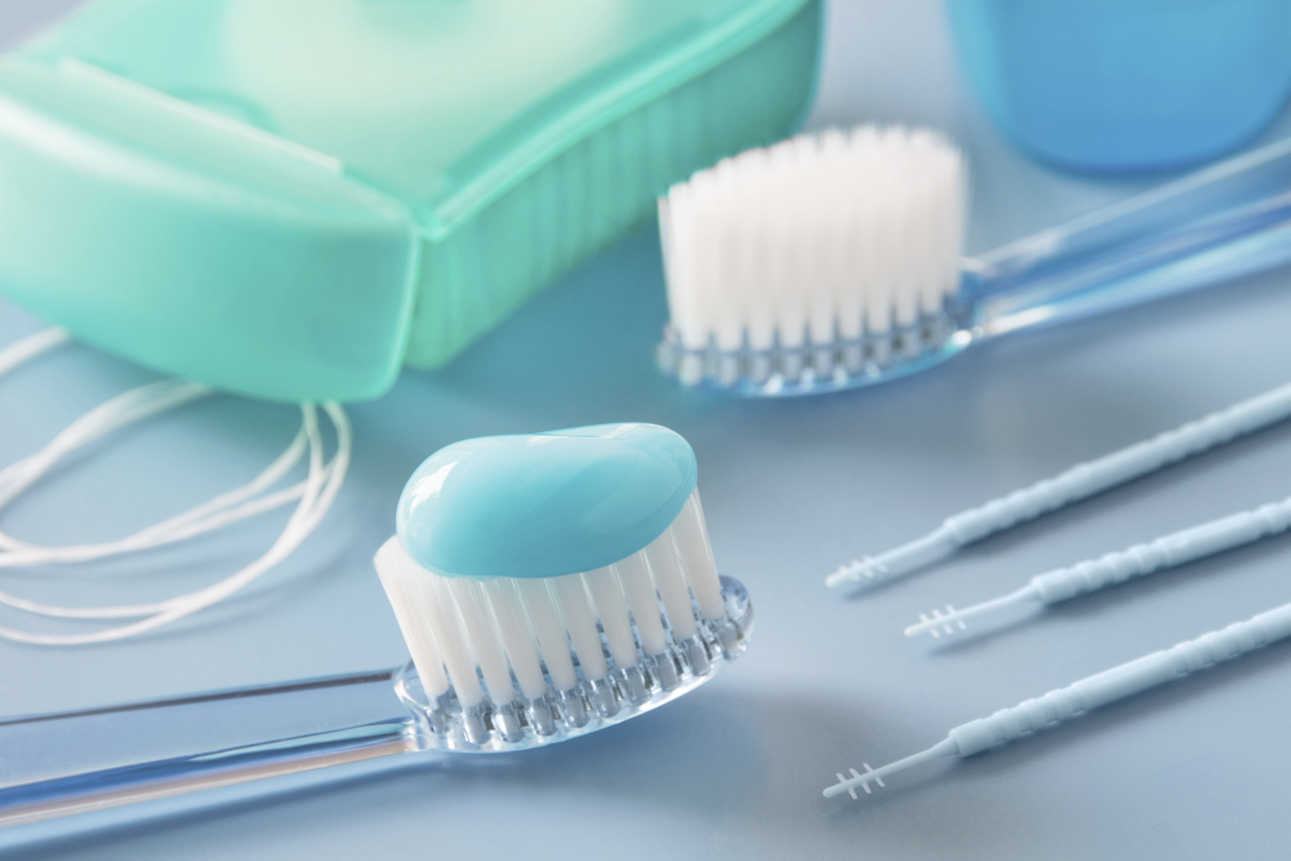 Toothbrushes with toothpaste on one of them in dental office and flossing tools