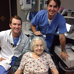 Drs. Bingham and Howarth your dentists in Tulsa standing with an older patient smiling