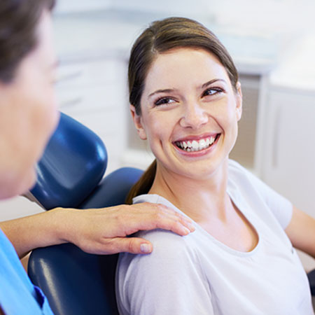 Young woman smiling in dental chair from sedation dentistry